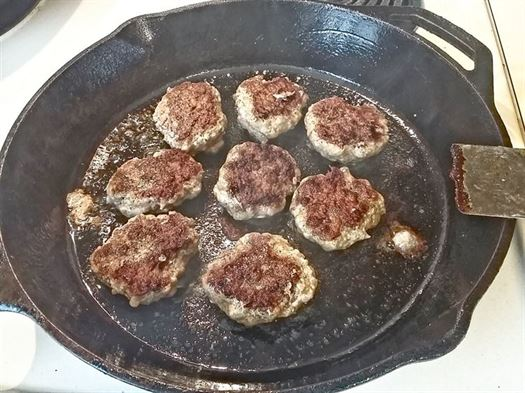 cooking sausage patties in cast iron skillet